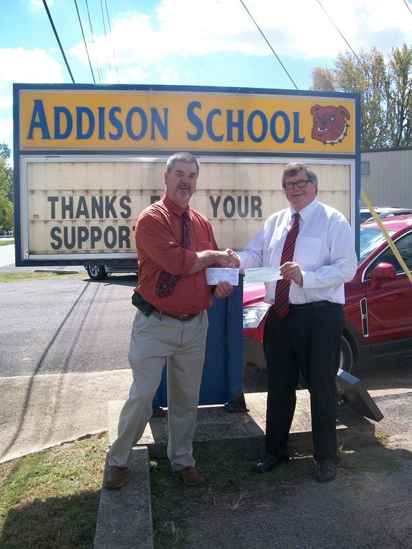 Rep. Tim Wadsworth gives 2 checks totaling $1000.00 to help fund a new sign for the Elementary School.